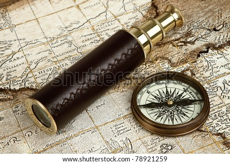 Vintage brass telescope on antique map with copy space - stock photo