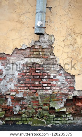 Vintage brick wall texture with damaged plaster and broken drainpipe - stock photo