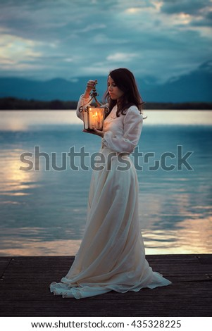 Vintage bride on lake pier with lantern. Romantic and surreal - stock photo