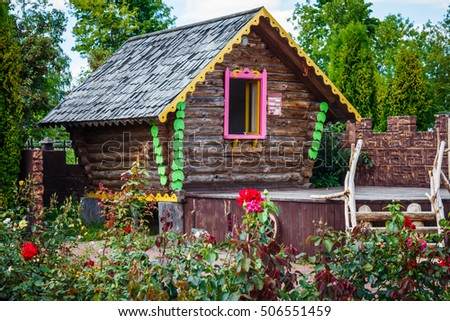 vintage bright wooden house in a park with trees and flowers