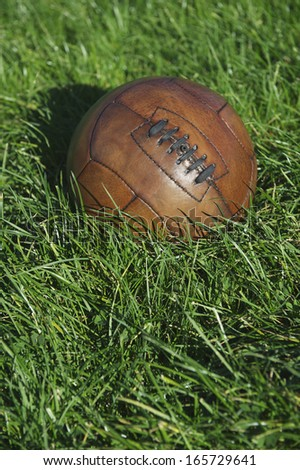 Vintage brown football soccer ball sits in sunny green grass field - stock photo