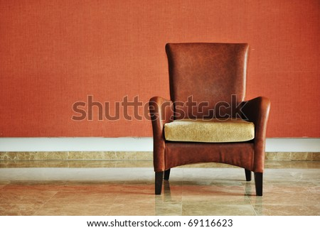 vintage brown-gray chair standing beside the wall - stock photo