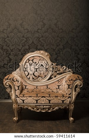 vintage brown-gray chair with gold accents standing beside the wall. wooden floor - stock photo