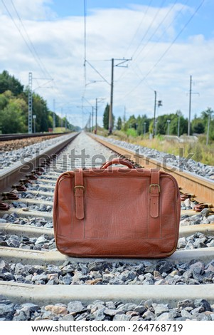 Vintage brown suitcase standing on the railway - stock photo