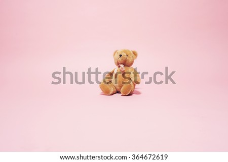 Vintage brown teddy bear with bow against pink background. - stock photo