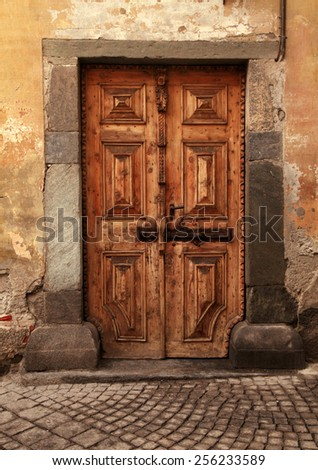 Vintage brown wood medieval door in rural stone wall house, Italy - stock photo