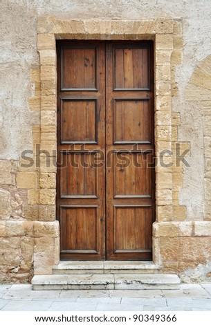 Vintage brown wooden door in Italy - stock photo