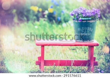 Vintage bucket with garden flowers on red little stool over summer nature background - stock photo