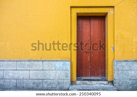 Vintage building with red wooden door and yellow concrete wall - stock photo