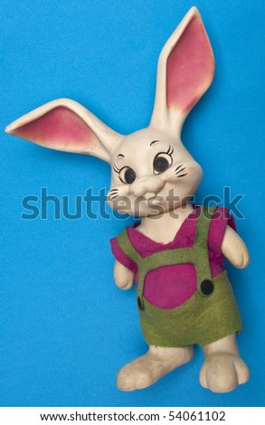 Vintage Bunny Toy Dressed in Colorful Lederhosen on a Blue Background.
