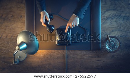Vintage business man holding the phone receiver, dialing a number and phone calling, top view - stock photo