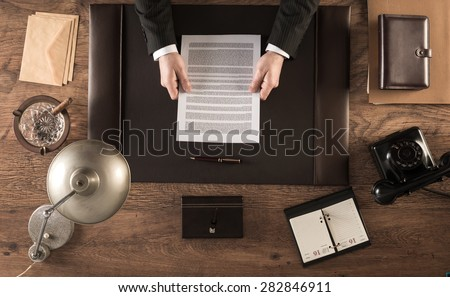 Vintage businessman in the office reading a contract sitting at his desk, top view - stock photo