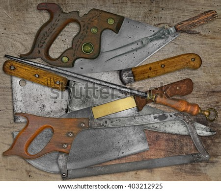 vintage butcher shop tools and utensils over stained wooden table - stock photo