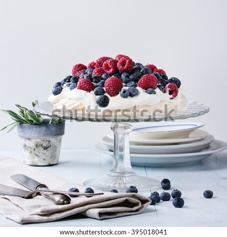 Vintage cake stand with Meringue dessert Pavlova with fresh blackberries and raspberries. Over blue wooden table with old tableware, textile napkin and snowdrops flowers. Square image