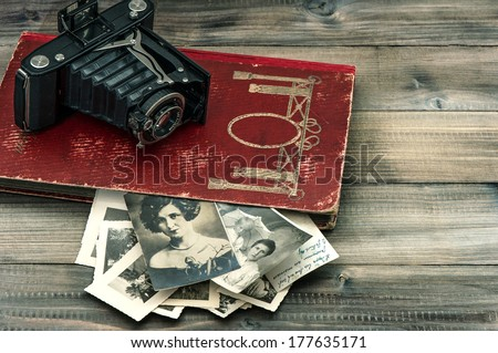 vintage camera and album with old photos on wooden table - stock photo