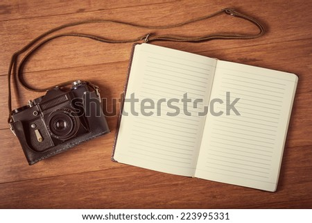 Vintage camera and open diary on wooden table. Instagram style toned photo. - stock photo