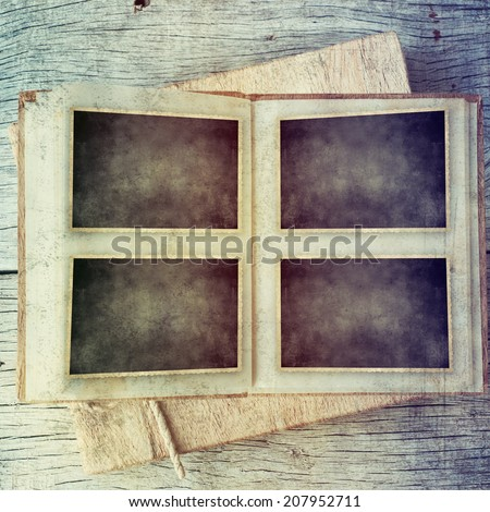 vintage camera and picture frame over wooden background - stock photo
