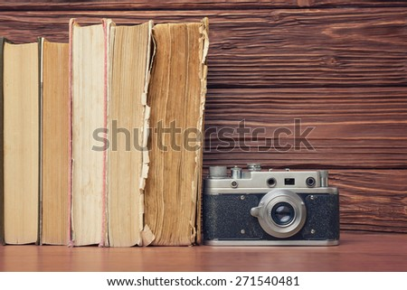 Vintage Camera and Stack of Books Over Wooden Background - stock photo