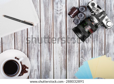 Vintage camera, diary with pan and cup pf coffee on wooden table