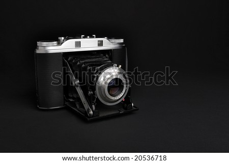 Vintage camera on a black background. - stock photo