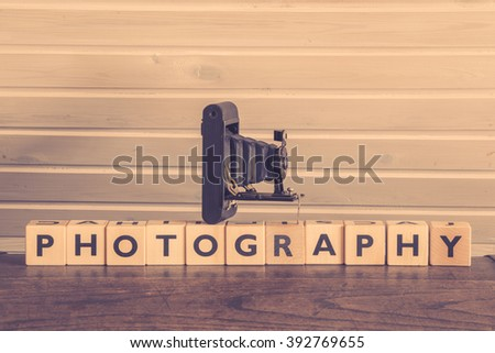 Vintage camera on a photography sign with wooden cubes - stock photo