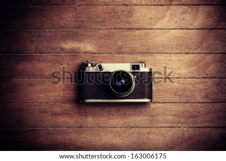 Vintage camera on a wooden background - stock photo