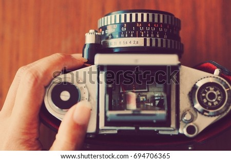 Vintage camera on wooden table background .