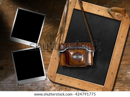 Vintage camera with leather case, two empty instant photo frames and a blank blackboard with wooden frame on a brown wall - stock photo