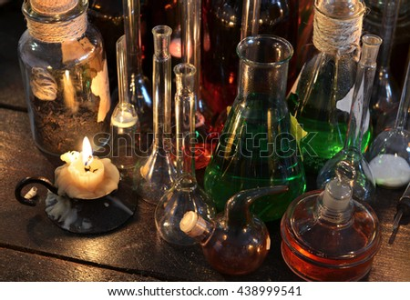 Vintage candle with old flasks and bottles on witch table. Old pharmacy, esoteric or alternative medicine concept. Black magic and occult objects, medieval alchemist ritual in ancient laboratory - stock photo