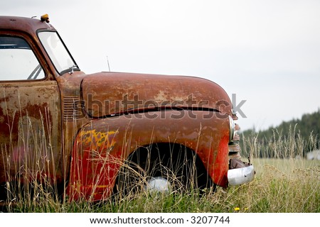vintage car abandoned in a field in rural Wyoming - stock photo