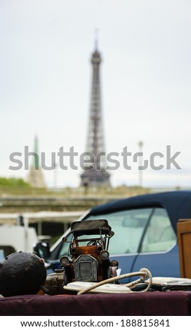 Vintage car model and other stuff at the flea market on the river Seine bank and Eiffel tower at background. Paris, France. - stock photo