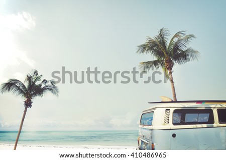 Vintage car parked on the tropical beach (seaside) with a surfboard on the roof - Leisure trip in the summer - stock photo