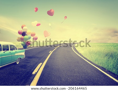 Vintage Car with heart balloon concept of love in summer and wedding honeymoon - stock photo