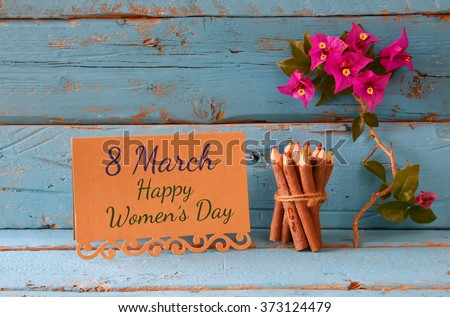 vintage card with phrase: 8 march happy womens day on wooden texture table next to purple bougainvillea flower.  - stock photo