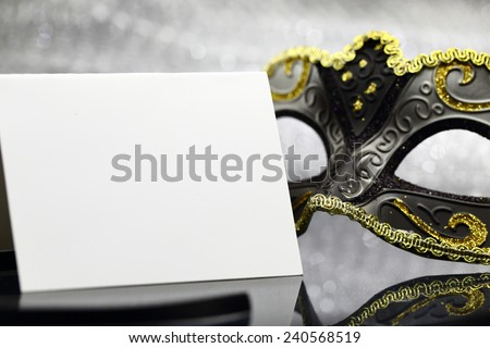 Vintage carnival mask and white blank card in front of glittering background - stock photo