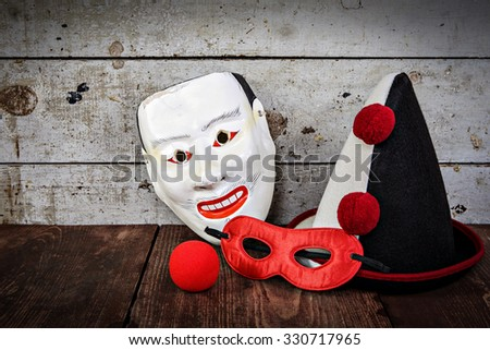 Vintage carnival masks, hat and nose, shallow focus, focus on clown hat. - stock photo