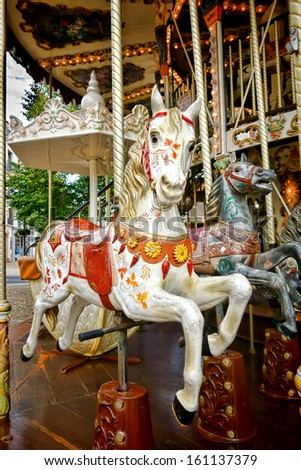 Vintage carved wood nostalgic carousel riding horse with antique painted decor mounted on a classic brass pole on an old amusement merry go round - stock photo