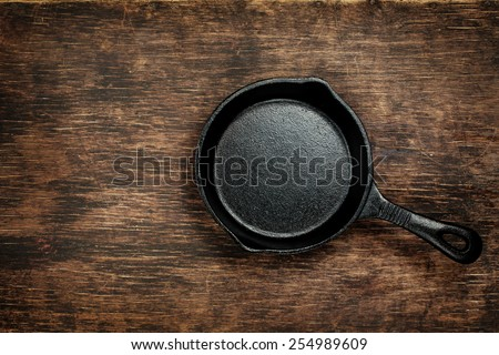 Vintage cast iron skillet on rustic wood background. Food background with copyspace - stock photo