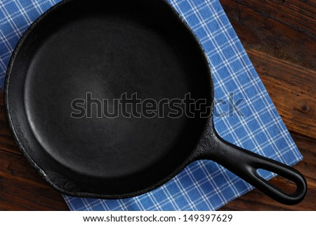 Vintage cast iron skillet with checkered kitchen towel on rustic wood background.  Low key still life with directional, natural lighting for effect. - stock photo