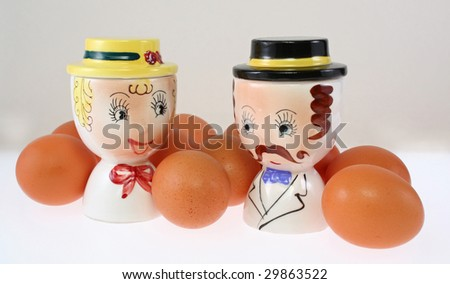 Vintage ceramic double egg cups surrounded by brown eggs - stock photo