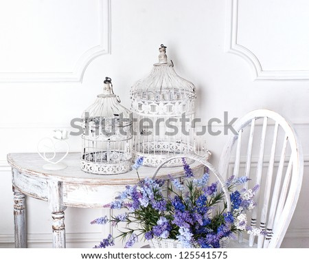 vintage chair and table with flower in front and cages - stock photo