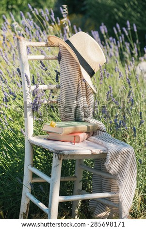 Vintage chair, books and hat in lavender field - stock photo