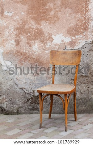 Vintage chair near old wall - stock photo