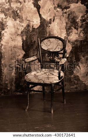Vintage chair on the background of shabby wall. Sepia colour graded.