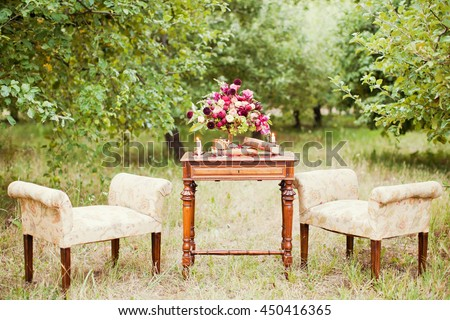 vintage chairs and table with flower composition - stock photo