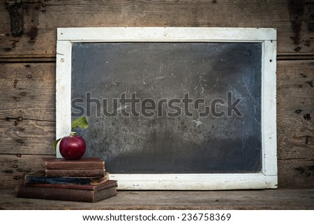 Vintage chalkboard with stack of books and apple on rustic wooden table and vintage filtered effect - stock photo