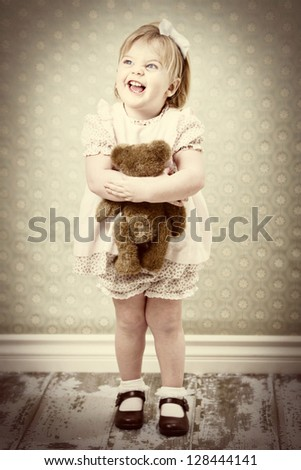 vintage child hugging her teddy bear - stock photo