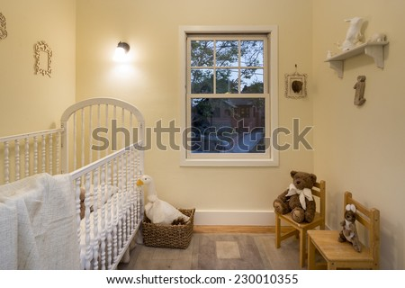 Vintage children bedroom / kids room with beige walls, carpet, chairs and bed  - stock photo
