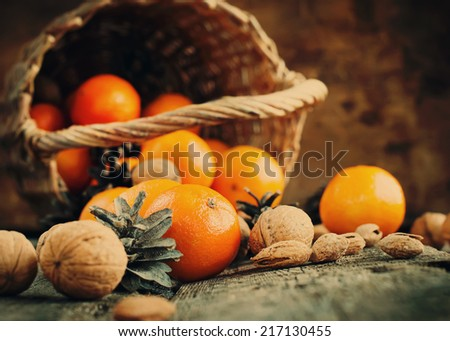 Vintage Christmas Composition with Basket, Food, Fruits and Nuts. Tangerines, Pine cones, Walnuts, Almonds are scattered on wooden background. Rural style, toned effect  - stock photo