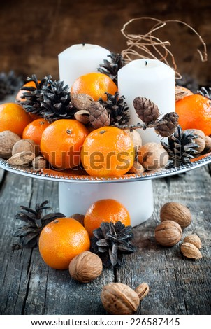 Vintage Christmas Decor for Table with Tangerines, Pine cones, Walnuts on Wooden Background holiday decoration - stock photo